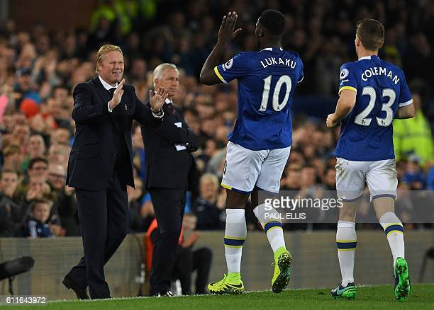 Everton's Belgian striker Romelu Lukaku celebrates scoring his team's first goal with Everton's Dutch manager Ronald Koeman during the English...