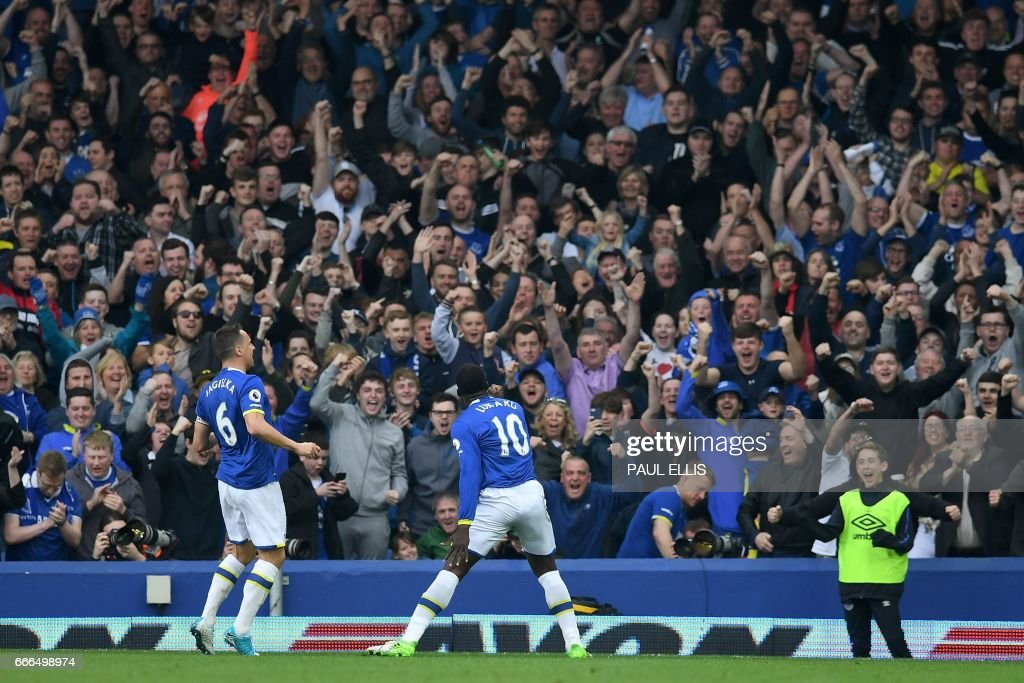 Everton's Belgian striker Romelu Lukaku (C) celebrates scoring his team's fourth goal during the English Premier League football match between Everton and Leicester City at Goodison Park in Liverpool, north west England on April 9, 2017. / AFP PHOTO / Paul ELLIS / RESTRICTED TO EDITORIAL USE. No use with unauthorized audio, video, data, fixture lists, club/league logos or 'live' services. Online in-match use limited to 75 images, no video emulation. No use in betting, games or single club/league/player publications. /
