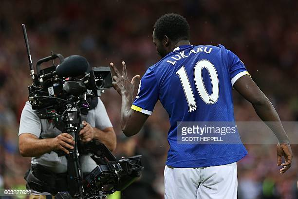 Everton's Belgian striker Romelu Lukaku gestures into the lens of a television camera as he celebrates scoring his team's third goal during the...