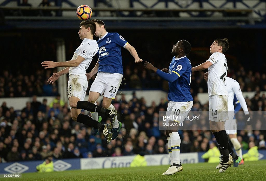 Everton's Belgian striker Romelu Lukaku (2R) watches as Everton's Irish defender Seamus Coleman (2L) heads the ball to score his team's first goal during the English Premier League football match between Everton and Swansea City at Goodison Park in Liverpool, north west England on November 19, 2016. / AFP / Oli SCARFF / RESTRICTED TO EDITORIAL USE. No use with unauthorized audio, video, data, fixture lists, club/league logos or 'live' services. Online in-match use limited to 75 images, no video emulation. No use in betting, games or single club/league/player publications. /