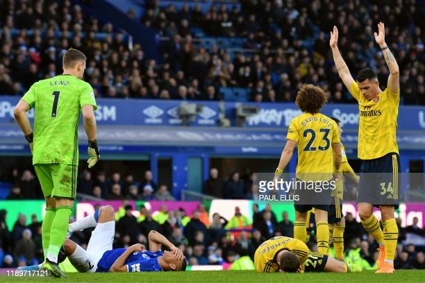 Everton's Brazilian striker Richarlison and Arsenal's English defender Calum Chambers lie injured on the pitch during the English Premier League...