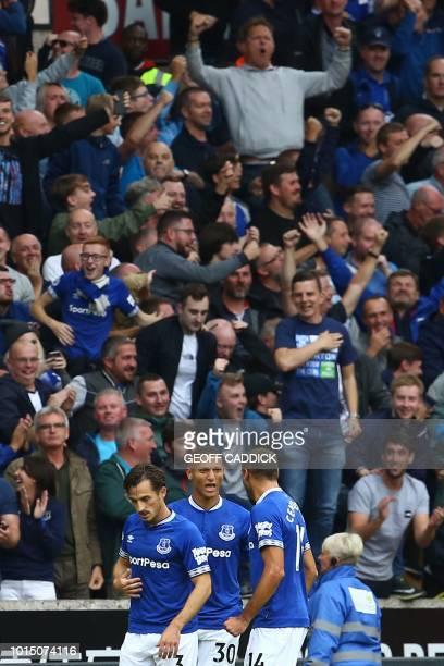 Everton's Brazilian striker Richarlison celebrates scoring the opening goal with Everton's English defender Leighton Baines and Everton's Turkish...