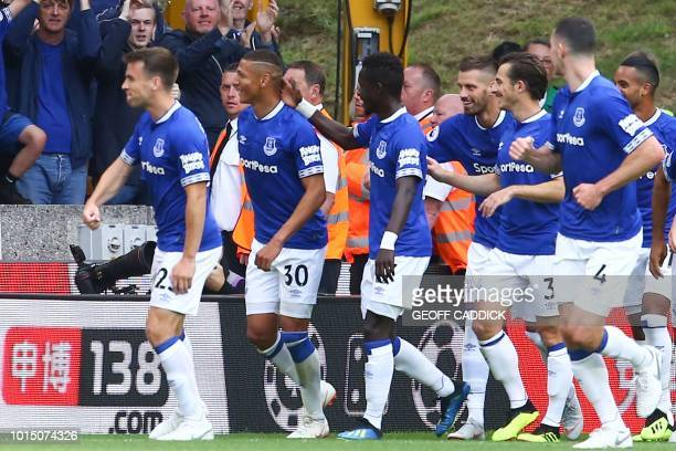 Everton's Brazilian striker Richarlison celebrates scoring the opening goal with Everton's English defender Leighton Baines during the English...