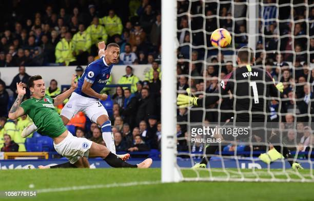 Everton's Brazilian striker Richarlison scores the opening goal during the English Premier League football match between Everton and Brighton and...