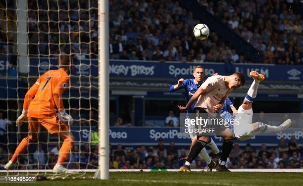 TOPSHOT Everton's Brazilian striker Richarlison scores the opening goal during the English Premier League football match between Everton and...