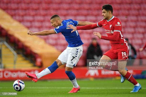 Everton's Brazilian striker Richarlison shoots, under pressure from Liverpool's Turkish defender Ozan Kabak to score the opening goal of the English...