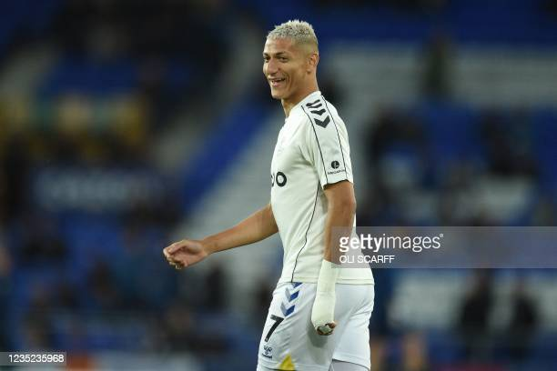 Everton's Brazilian striker Richarlison smiles as he warms up ahead of the English Premier League football match between Everton and Burnley at...