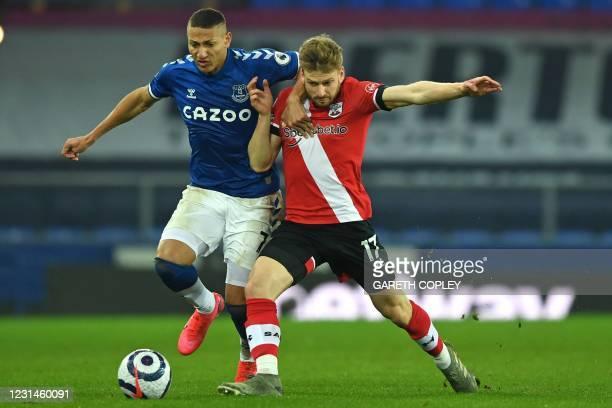Everton's Brazilian striker Richarlison vies with Southampton's Scottish midfielder Stuart Armstrong during the English Premier League football match...