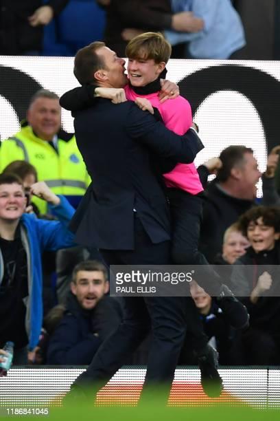 Everton's caretaker manager Duncan Ferguson embraces a ballboy as he celebrates on the touchline after Everton's English striker Dominic CalvertLewin...