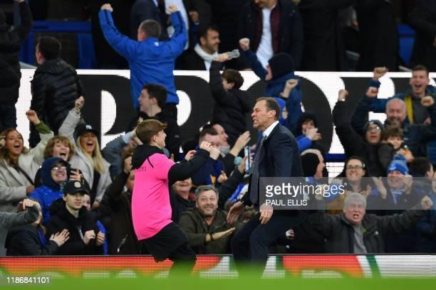 Everton's caretaker manager Duncan Ferguson runs to embrace a ballboy as he celebrates on the touchline after Everton's English striker Dominic...