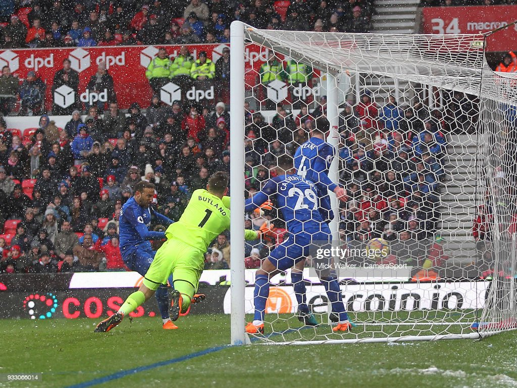 Everton's Cenk Tosun scores his sides first goal beating Stoke City's Jack Butland during the Premier League match between Stoke City and Everton at Bet365 Stadium on March 17, 2018 in Stoke on Trent, England.