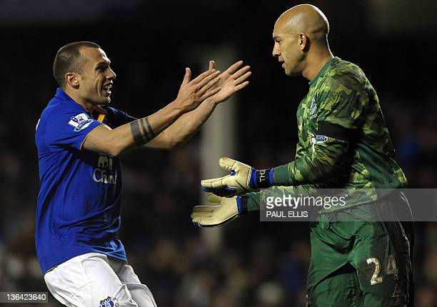 Everton's Dutch midfielder John Heitinga congratulates Everton's American goalkeeper Tim Howard after the keeper scored from his own goal area during...