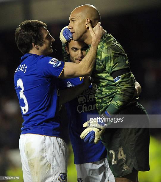 Everton's English defender Leighton Baines and Everton's US forward Landon Donovan congratulate Everton's American goalkeeper Tim Howard after the...