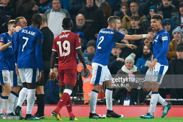 Everton's English defender Mason Holgate is restrained by Everton's French midfielder Morgan Schneiderlin after a flare up between Holgate and...