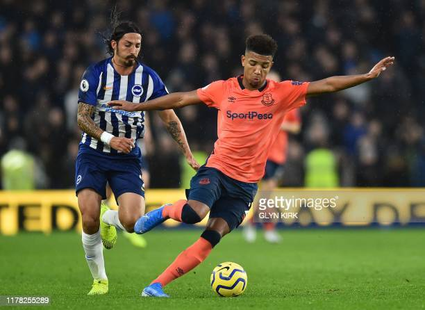 Everton's English defender Mason Holgate turns away Everton's Portuguese midfielder André Gomes during the English Premier League football match...