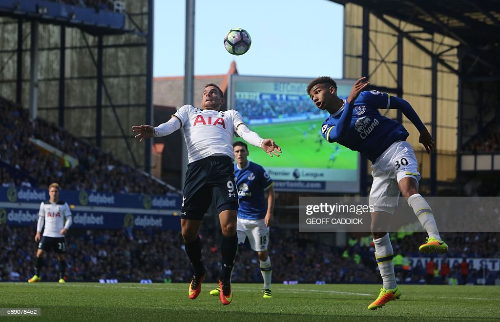 Everton's English defender Mason Holgate (R) vies with Tottenham Hotspur's Dutch striker Vincent Janssen (L) during the English Premier League football match between Everton and Tottenham Hotspur at Goodison Park in Liverpool, north west England on August 13, 2016. / AFP / GEOFF CADDICK / RESTRICTED TO EDITORIAL USE. No use with unauthorized audio, video, data, fixture lists, club/league logos or 'live' services. Online in-match use limited to 75 images, no video emulation. No use in betting, games or single club/league/player publications. /