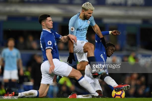 Everton's English defender Michael Keane and Everton's Senegalese midfielder Idrissa Gueye tackle Manchester City's Argentinian striker Sergio Aguero...