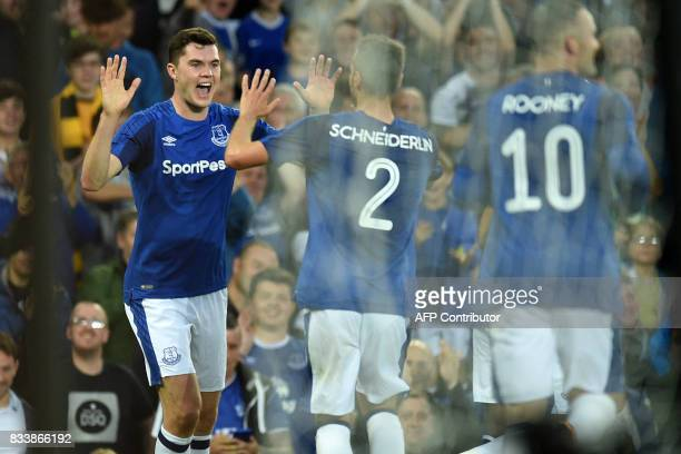 Everton's English defender Michael Keane celebrates with teammates after scoring the opening goal during the UEFA Europa League playoff round first...