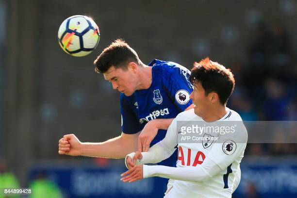 Everton's English defender Michael Keane heads the ball under pressure from Tottenham Hotspur's South Korean striker Son HeungMin during the English...
