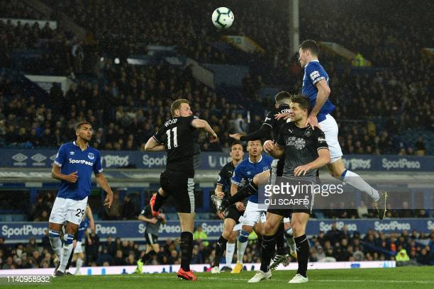 Everton's English defender Michael Keane jumps to win a header but it is easily saved during the English Premier League football match between...