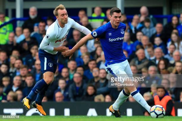 Everton's English defender Michael Keane passes the ball under pressure from Tottenham Hotspur's Danish midfielder Christian Eriksen during the...