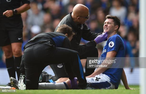Everton's English defender Michael Keane receives medical treatment during the English Premier League football match between Everton and Stoke City...