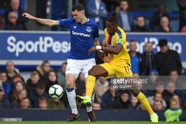 Everton's English defender Michael Keane vies with Crystal Palace's Ivorian striker Wilfried Zaha during the English Premier League football match...