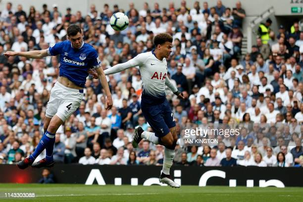Everton's English defender Michael Keane wins a header defended by Tottenham Hotspur's English midfielder Dele Alli during the English Premier League...