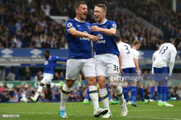 Everton's English defender Phil Jagielka celebrates scoring his team's third goal with Everton's English defender Matthew Pennington during the...