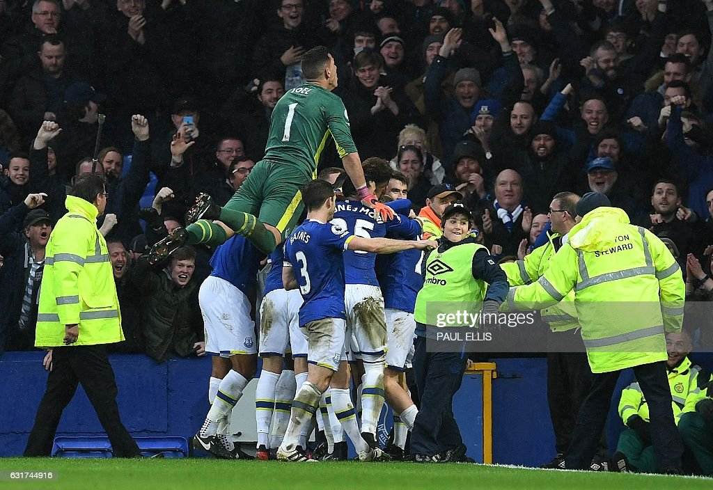 Everton's English forward Ademola Lookman is mobbed by teammates as he celebrates scoring his team's fourth goal during the English Premier League football match between Everton and Manchester City at Goodison Park in Liverpool, north-west England on January 15, 2017. Everton won the match 4-0. / AFP / Paul ELLIS / RESTRICTED TO EDITORIAL USE. No use with unauthorized audio, video, data, fixture lists, club/league logos or 'live' services. Online in-match use limited to 75 images, no video emulation. No use in betting, games or single club/league/player publications. /