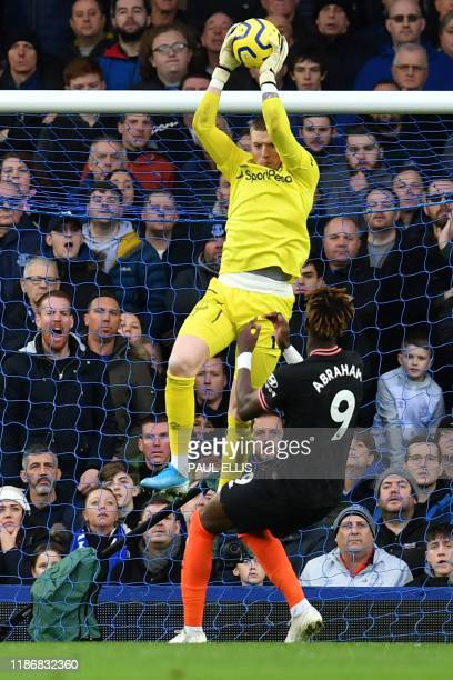 Everton's English goalkeeper Jordan Pickford catches the ball under pressure from Chelsea's English striker Tammy Abraham during the English Premier...