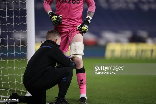 Everton's English goalkeeper Jordan Pickford gets some attention to his leg with strapping on it during the English Premier League football match...