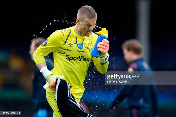 Everton's English goalkeeper Jordan Pickford sprays water on his face during the English Premier League football match between Everton and Aston...