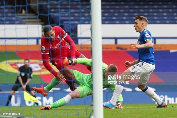 Everton's English goalkeeper Jordan Pickford tackles Liverpool's Dutch defender Virgil van Dijk during the English Premier League football match...