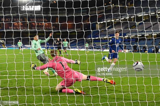 Everton's English midfielder Ben Godfrey diverts a shot from Chelsea's German midfielder Kai Havertz into his own net for the opening goal of the...