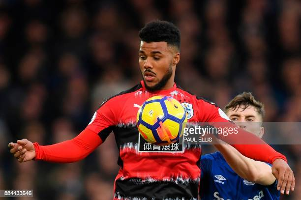 Everton's English midfielder Jonjoe Kenny challenges Huddersfield Town's German striker Elias Kachunga during the English Premier League football...