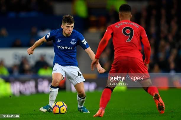 Everton's English midfielder Jonjoe Kenny takes on Huddersfield Town's German striker Elias Kachunga during the English Premier League football match...