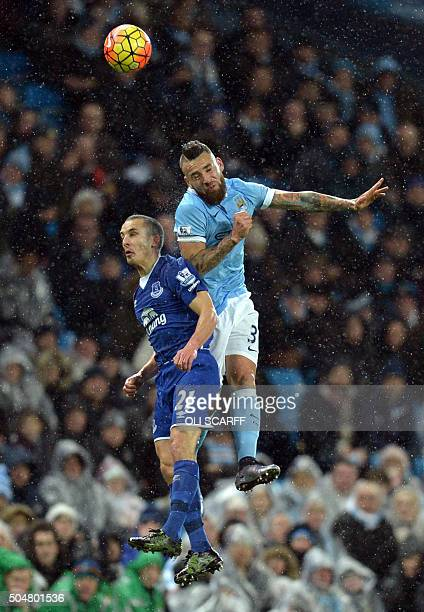 Everton's English midfielder Leon Osman jumps for a header with Manchester City's Argentinian defender Nicolas Otamendi during the English Premier...