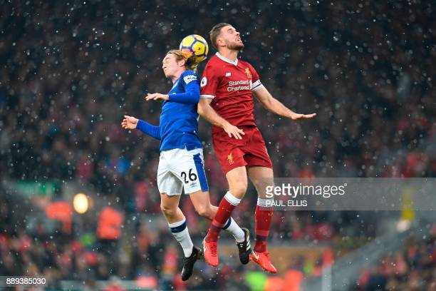 Everton's English midfielder Tom Davies jumps against Liverpool's English midfielder Jordan Henderson during the English Premier League football...