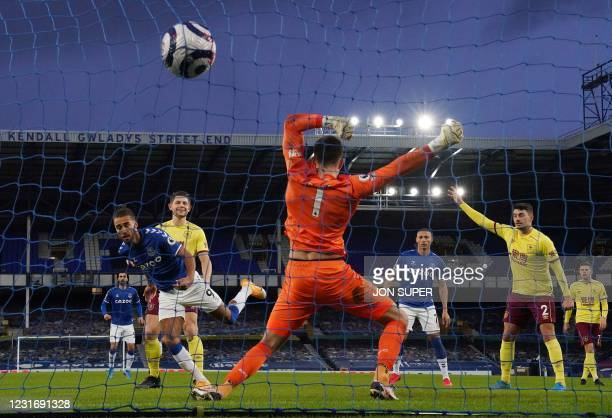 Everton's English striker Dominic Calvert-Lewin scores past Burnley's English goalkeeper Nick Pope during the English Premier League football match...