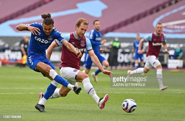 Everton's English striker Dominic Calvert-Lewin shoots to score his team's first goal as West Ham United's English defender Craig Dawson closes in...