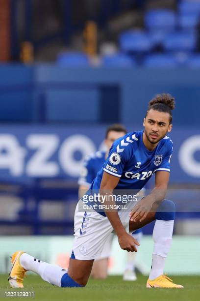 Everton's English striker Dominic Calvert-Lewin 'takes a knee' in support of the No Room For Racism campaign ahead of the English Premier League...