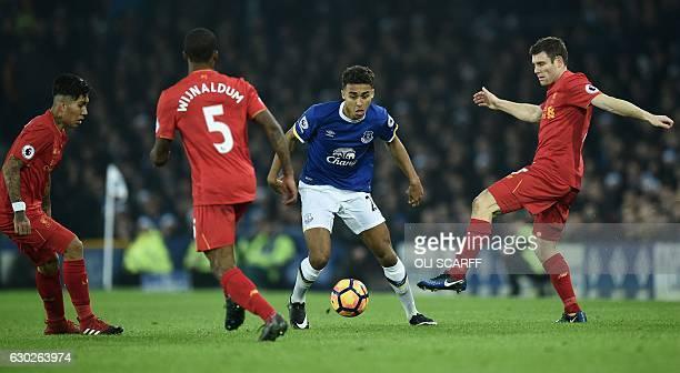 Everton's English striker Dominic Calvert-Lewin vies with Liverpool's Dutch midfielder Georginio Wijnaldum and Liverpool's English midfielder James...
