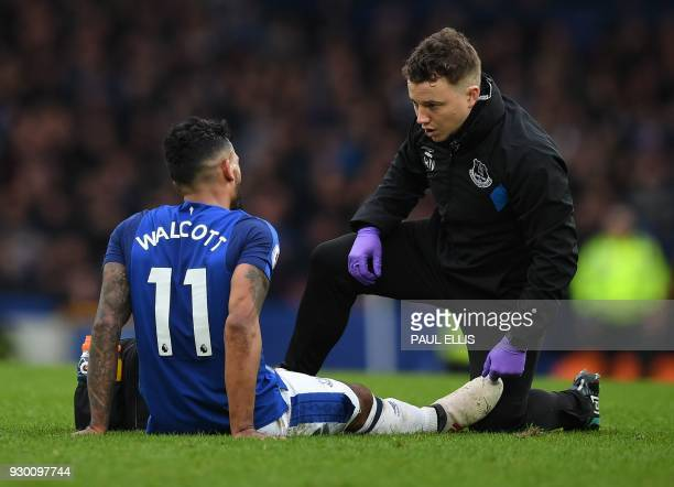 Everton's English striker Theo Walcott receives medical treatment during the English Premier League football match between Everton and Brighton and...