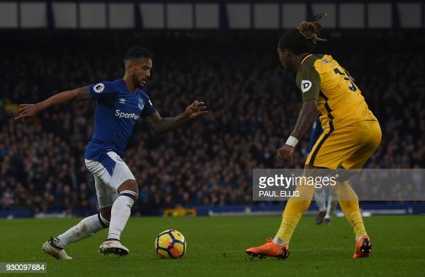Everton's English striker Theo Walcott vies with Brighton's Cameroonian defender Gaetan Bong during the English Premier League football match between...