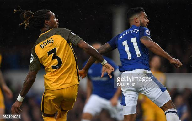 Everton's English striker Theo Walcott vies with Brighton's Cameroonian defender Gaetan Bong as he scores his team's first goal during the English...