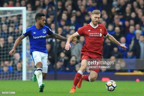 Everton's English striker Theo Walcott vies with Liverpool's Estonian defender Ragnar Klavan during the English Premier League football match between...