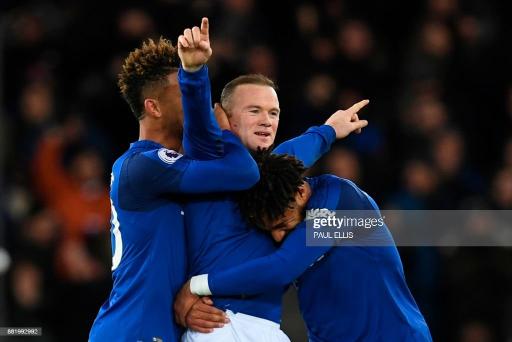TOPSHOT - Everton's English striker Wayne Rooney (C) celebrates scoring his third goal to complete his hattrick during the English Premier League football match between Everton and West Ham United at Goodison Park in Liverpool, north west England on November 29, 2017. / AFP PHOTO / Paul ELLIS / RESTRICTED TO EDITORIAL USE. No use with unauthorized audio, video, data, fixture lists, club/league logos or 'live' services. Online in-match use limited to 75 images, no video emulation. No use in betting, games or single club/league/player publications. /