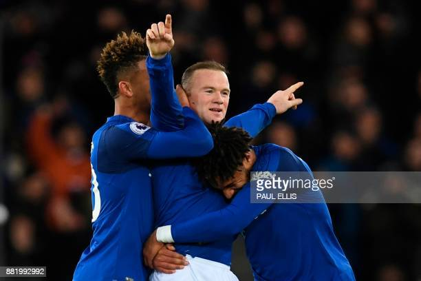 TOPSHOT Everton's English striker Wayne Rooney celebrates scoring his third goal to complete his hattrick during the English Premier League football...