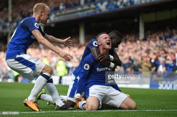 Everton's English striker Wayne Rooney celebrates scoring the opening goal with Everton's Dutch midfielder Davy Klaassen and Everton's Senegalese...